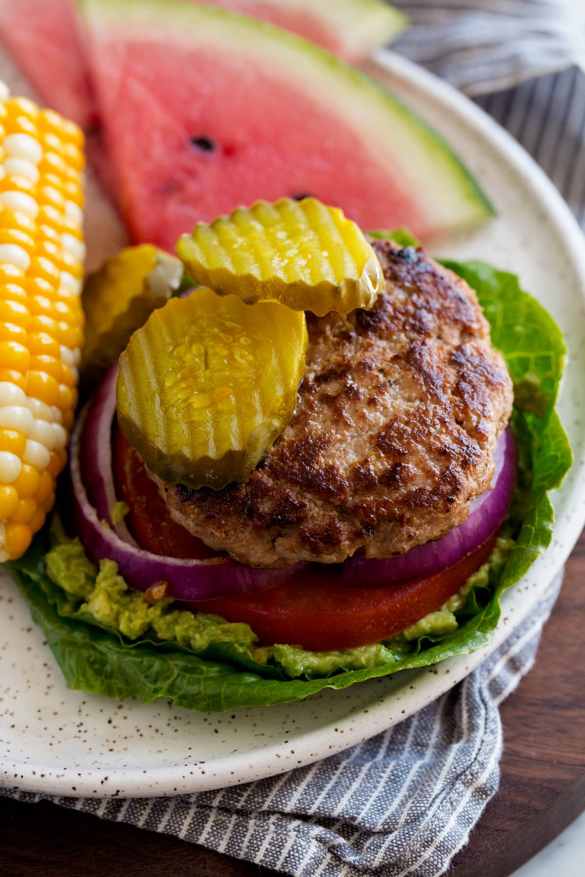 Low carb open faced turkey burger on lettuce leaves. Served with a side of corn and watermelon.