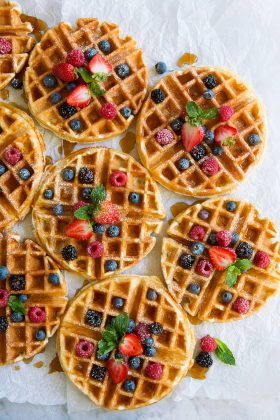 Eight Belgian Waffles topped with berries and maple syrup.