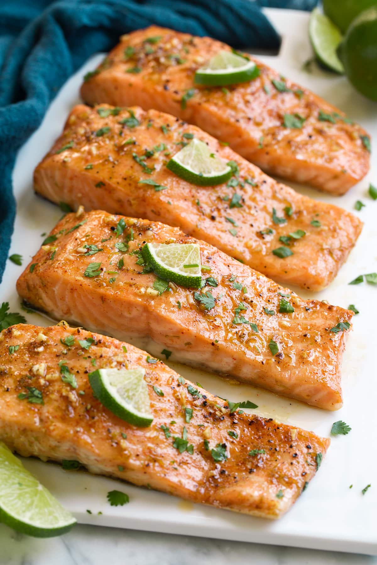 Baked salmon on a white serving platter. It's topped with a brown sugar and lime sauce and garnished with limes and cilantro.