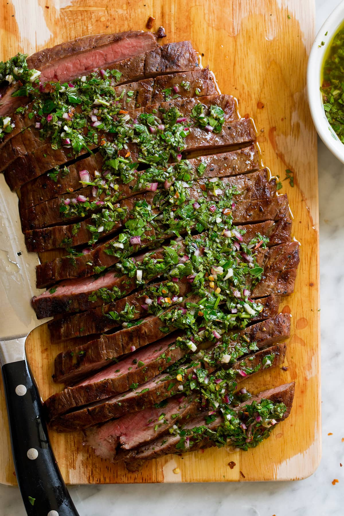 Showing a serving suggestion for homemade chimichurri, serving it over sliced steak.