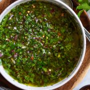 Overhead close up image of chimichurri in a bowl set over a wooden plate on a marble surface.