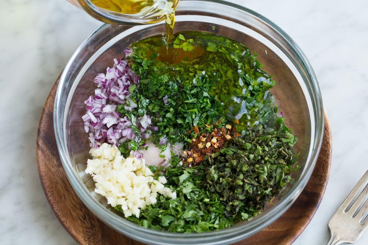 Chỉ ra cách làm chimichurri. Trộn rau mùi tây, rau mùi, lá oregano, hành tây, tỏi, mảnh ớt đỏ, dầu ô liu, chanh và giấm rượu vang đỏ trong một bát trộn thủy tinh.