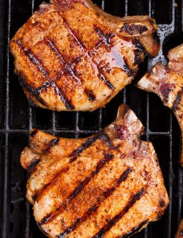 Overhead close up image of two pork chops on a grill.