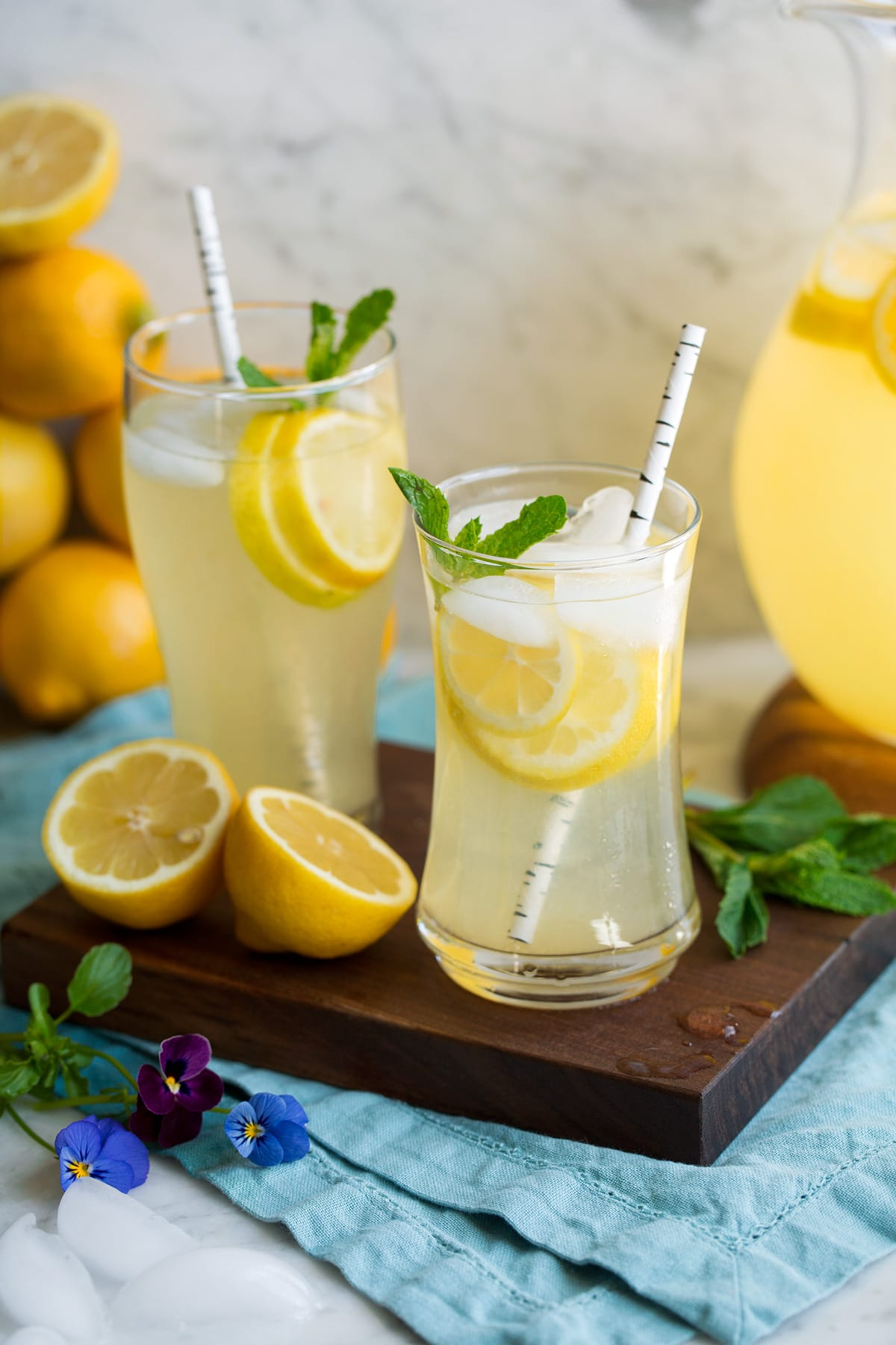 Two glasses of lemonade on a wooden platter.