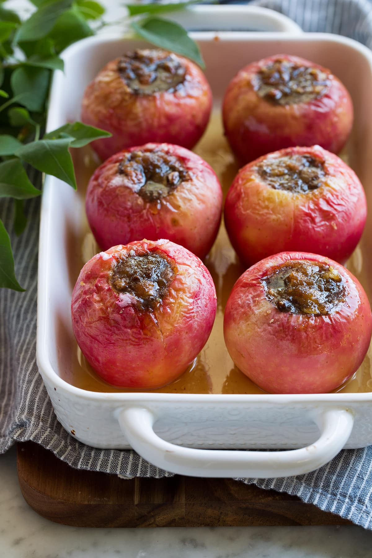 Six baked apples filled with brown sugar filling in a baking dish.