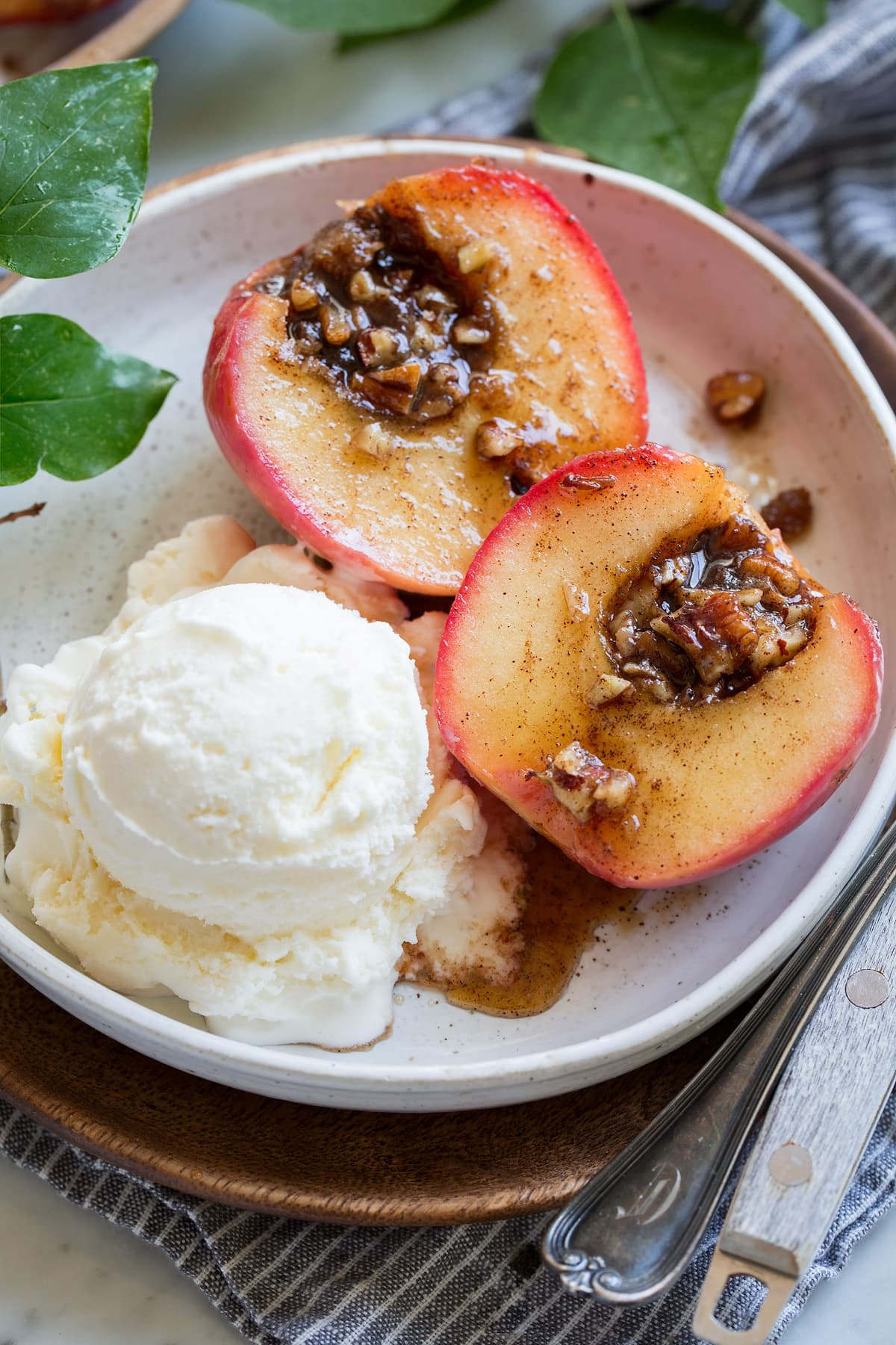 Baked apple sliced in half showing brown sugar pecan filling. Served with a side of vanilla ice cream.