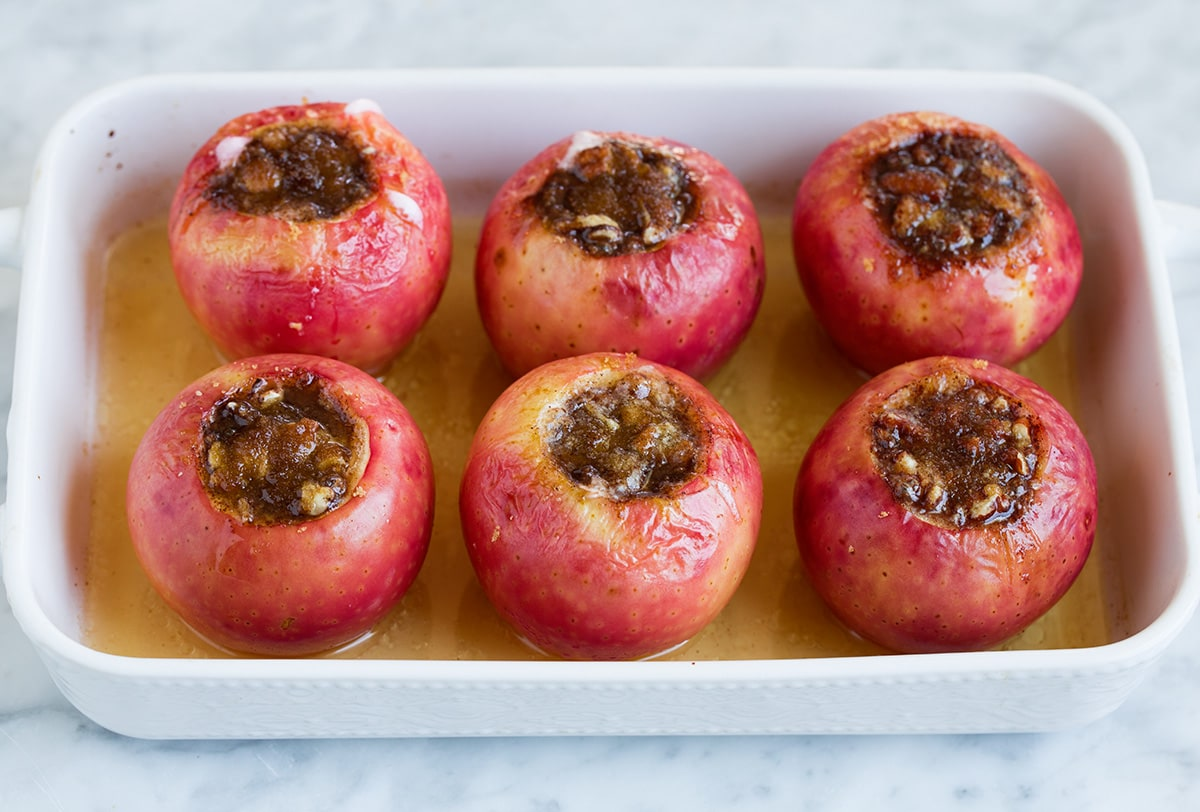 Apples shown after baking in baking dish with apple juice on bottom.