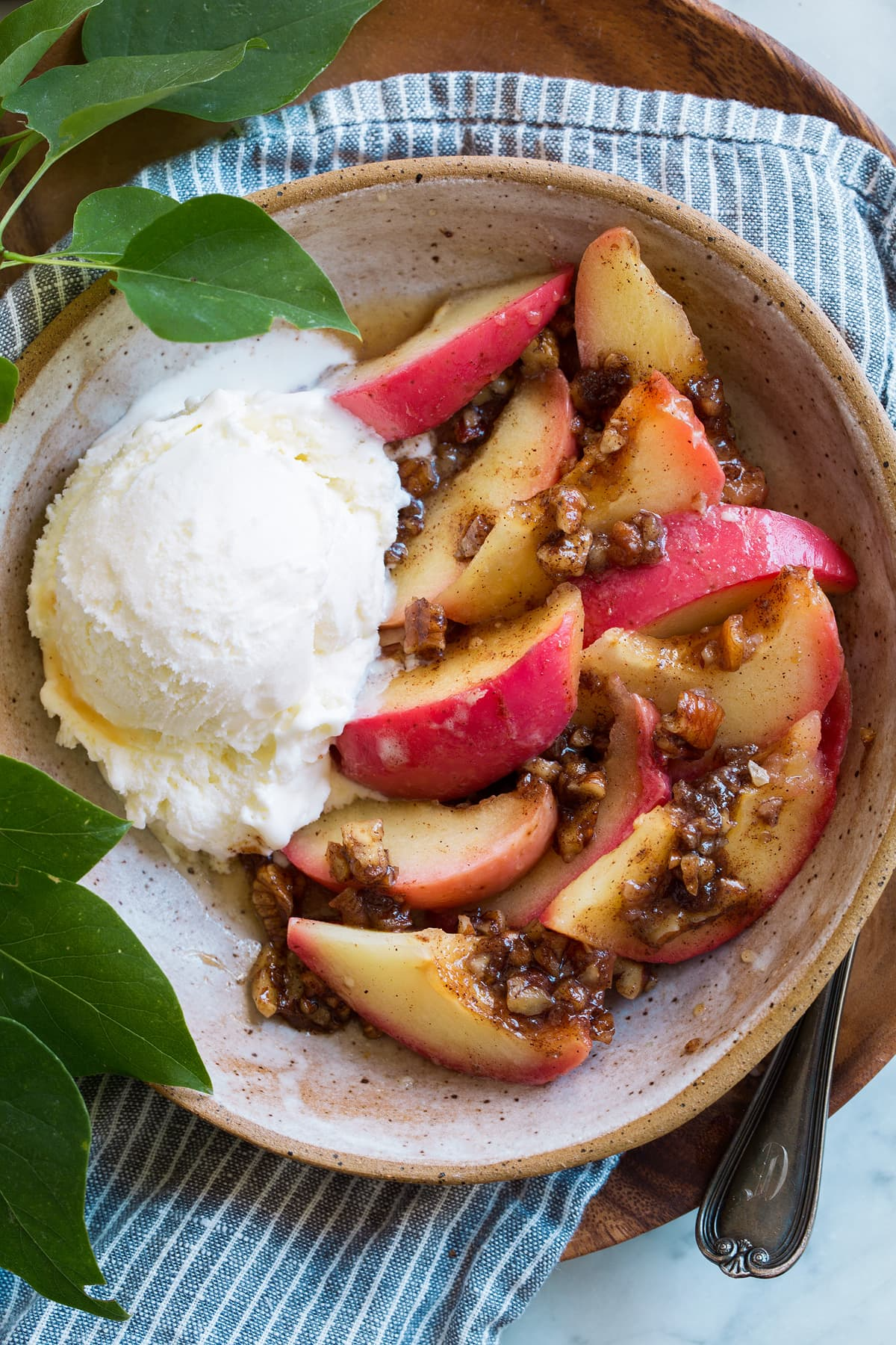 Baked apple cut into slices with pecan filling over top and a side of vanilla ice cream.