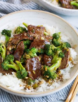 Beef and broccoli over white rice in a bowl.