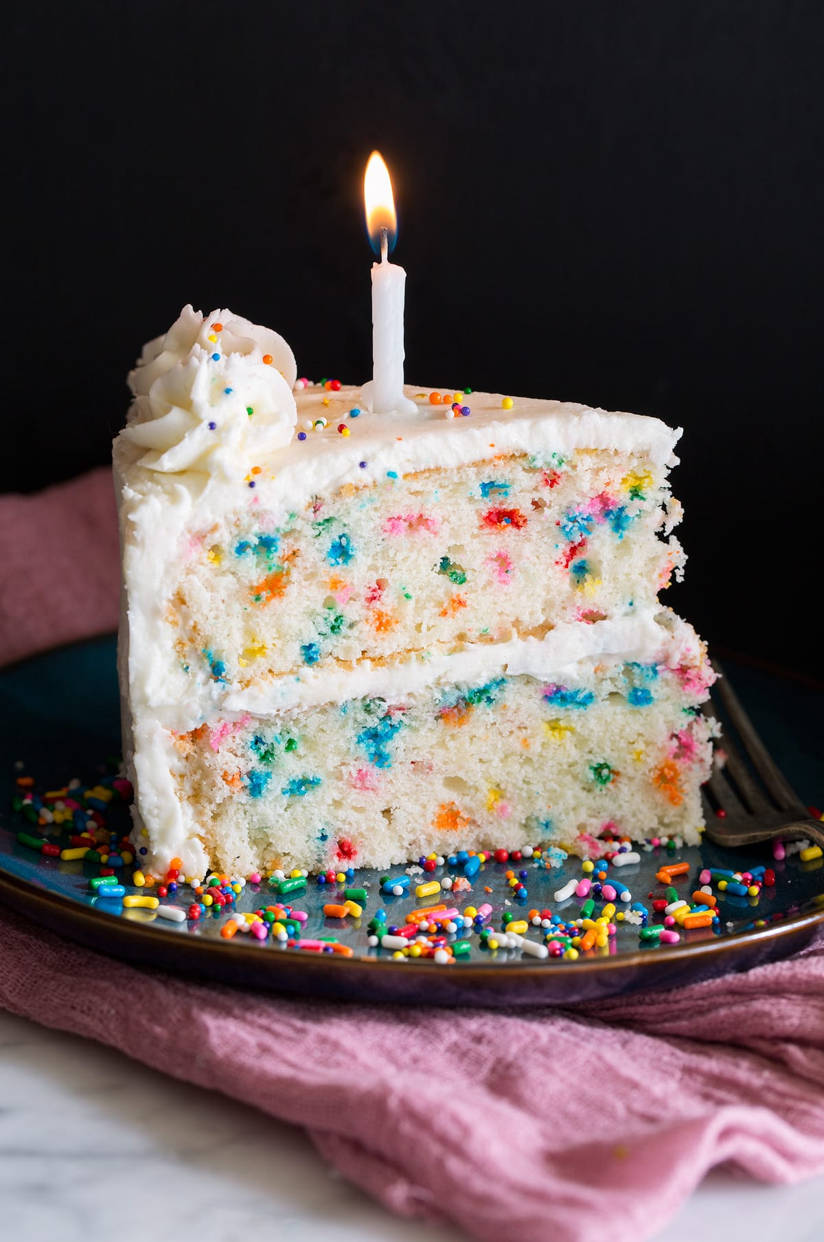 Slice of birthday cake with multi color dots in cake and topped with buttercream frosting and a birthday. candle.