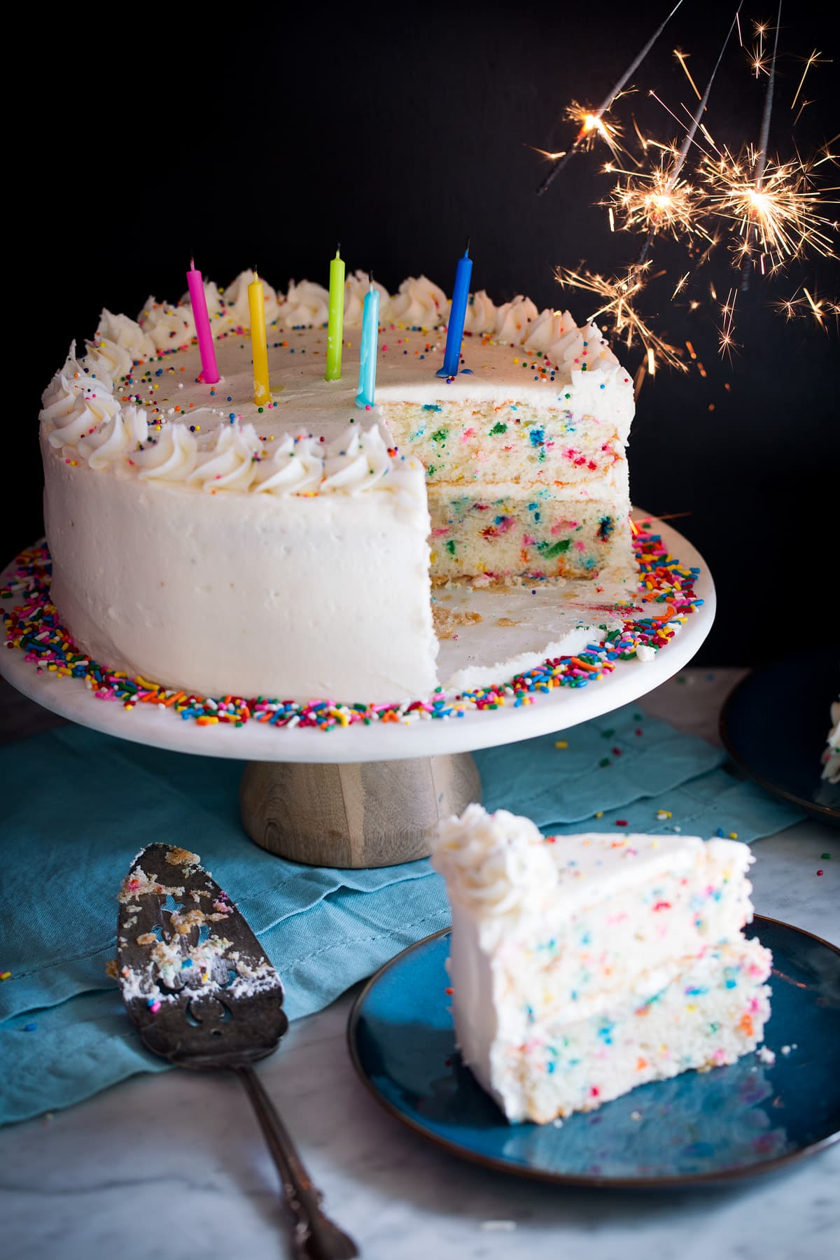 Birthday cake topped with candles and sparklers to the side.