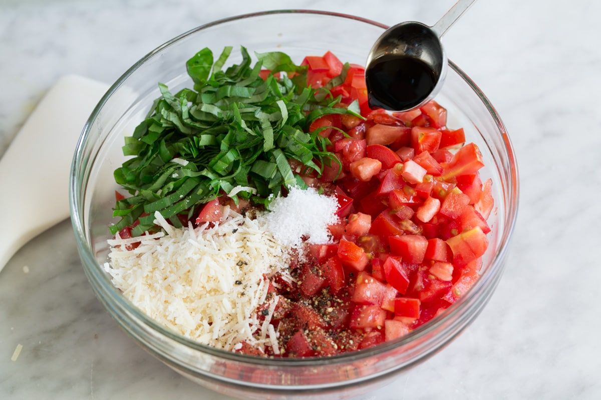 Bruschetta ingredients in a glass mixing bowl before mixing
