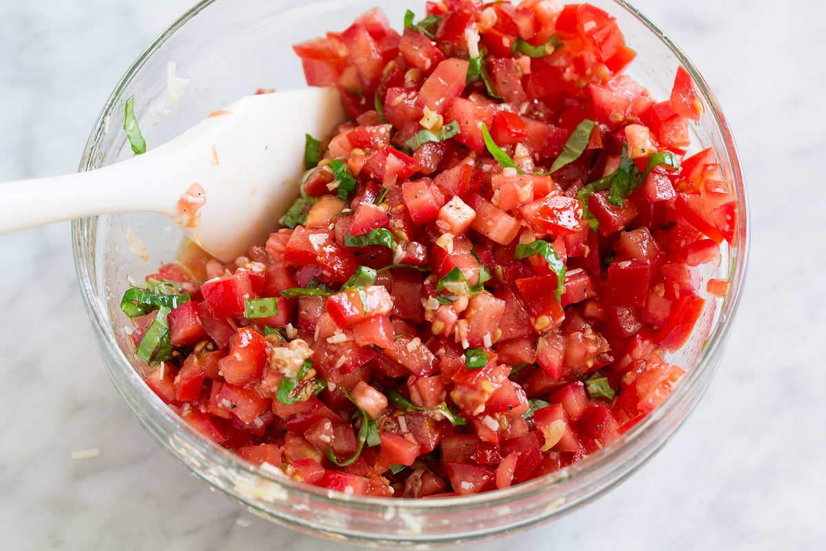 Tomato bruschetta mixture in a glass mixing bowl