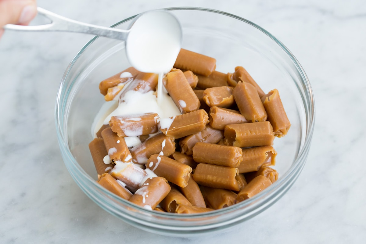 adding cream to caramels in glass bowl