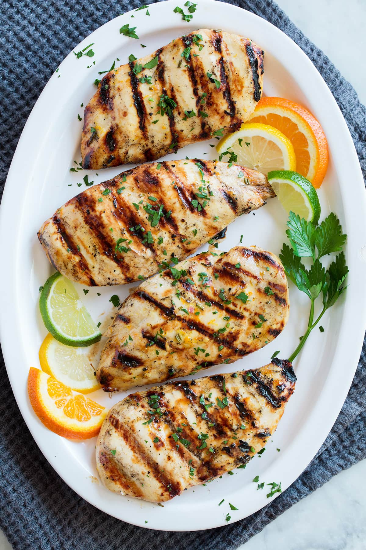 Overhead image of chicken breasts coated with marinade on a serving platter.