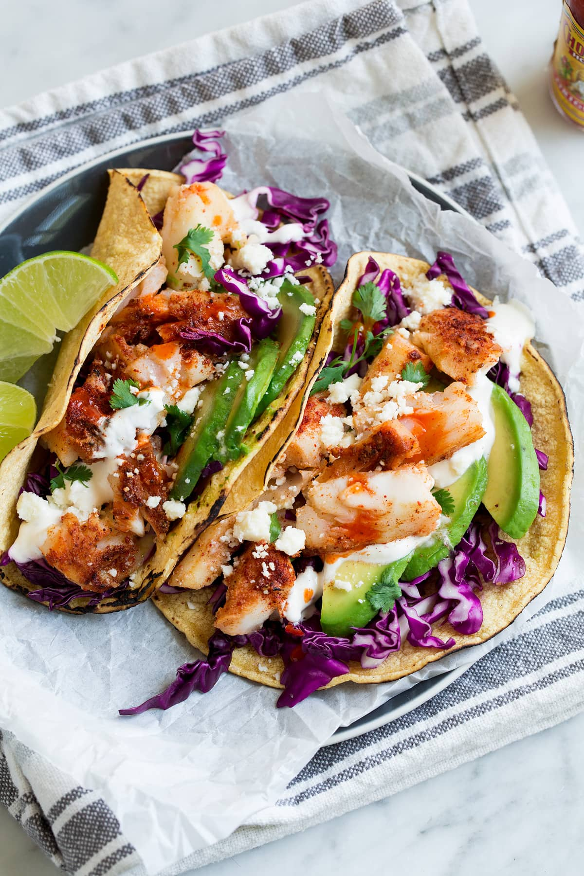Two fish tacos on parchment paper on a plate.