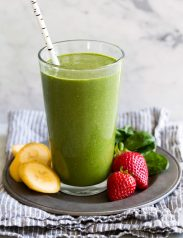 Green smoothie in a tall glass with strawberries, spinach and bananas to the side.