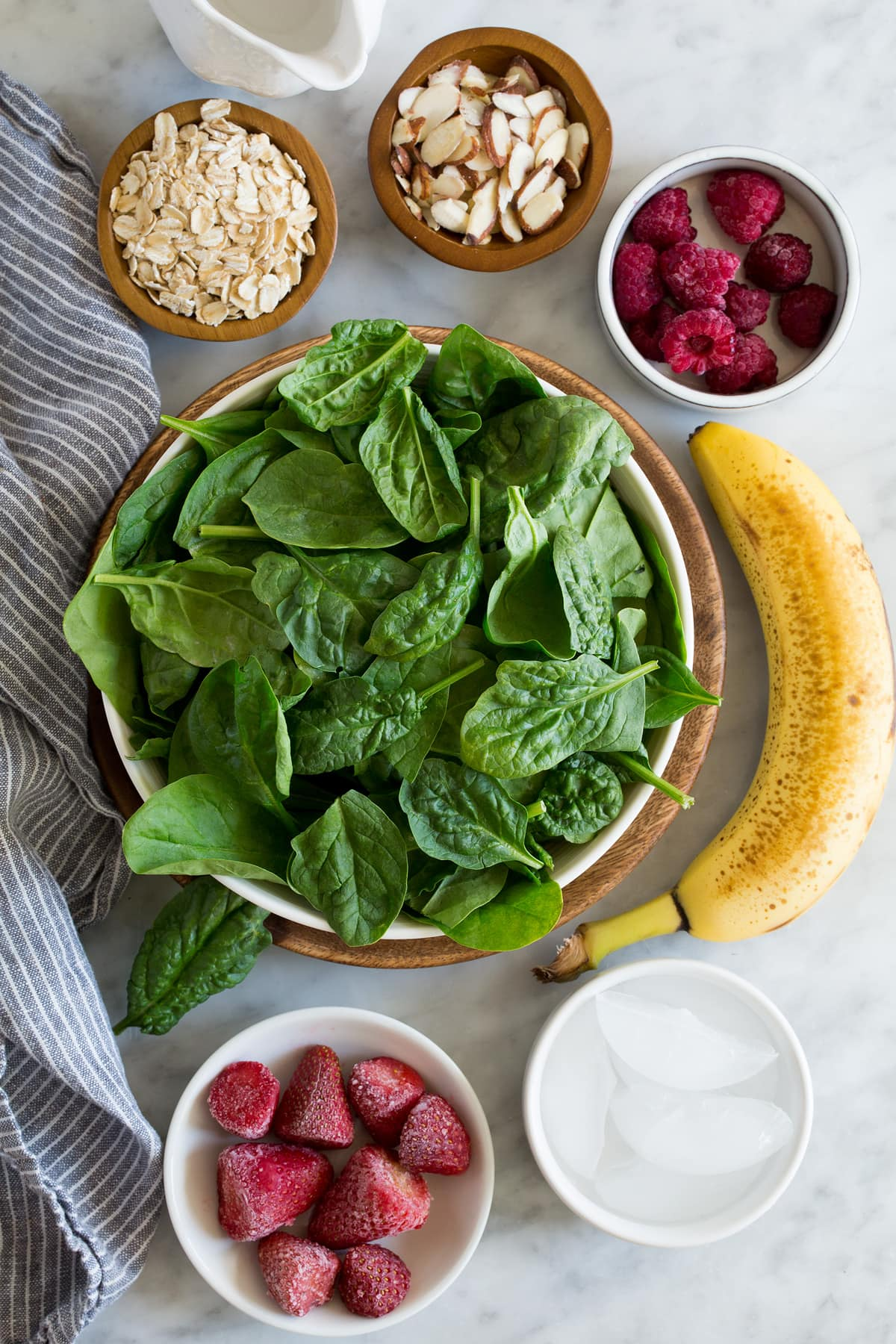 Ingredients needed to make green smoothie shown here including spinach, strawberries, raspberries, bananas, almonds, oats, water, and ice.