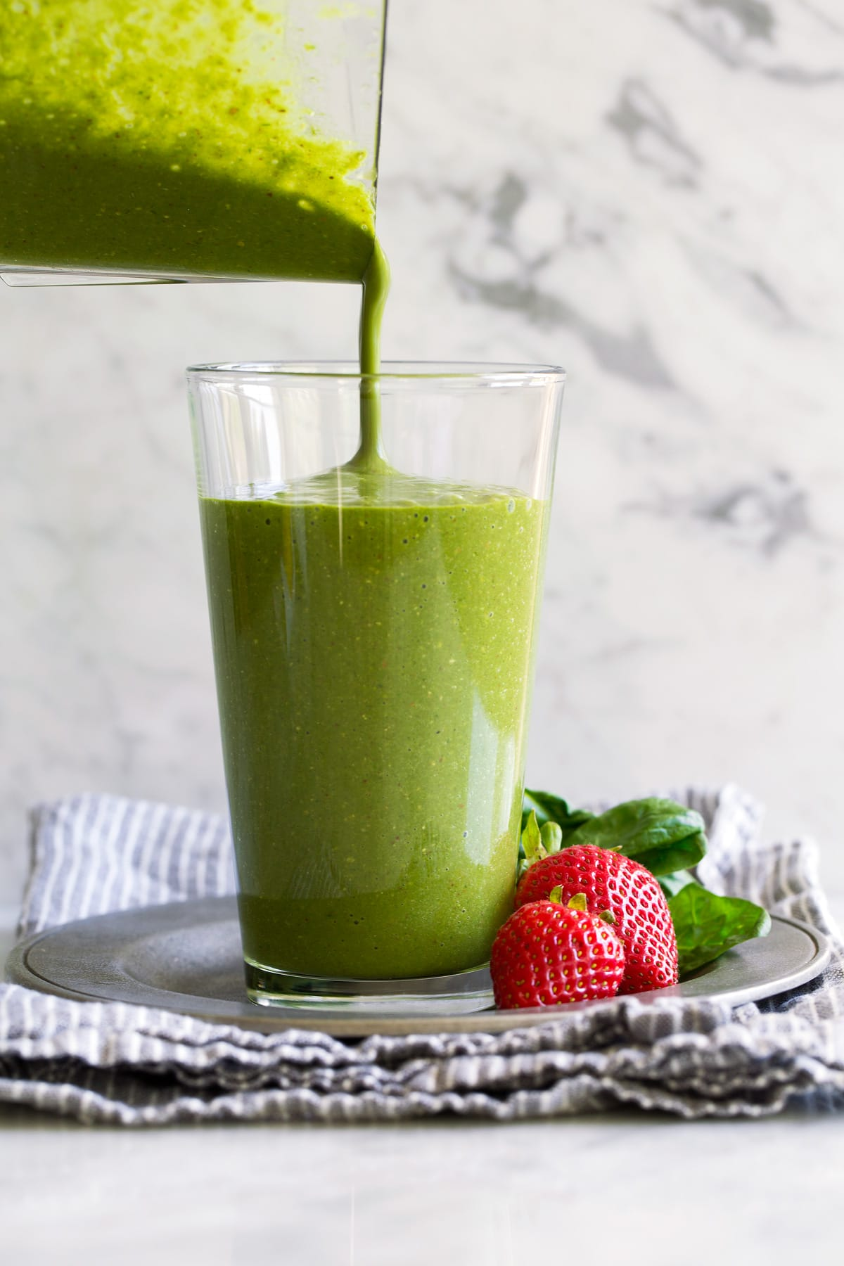 Pouring green smoothie into a glass from a blender jar.