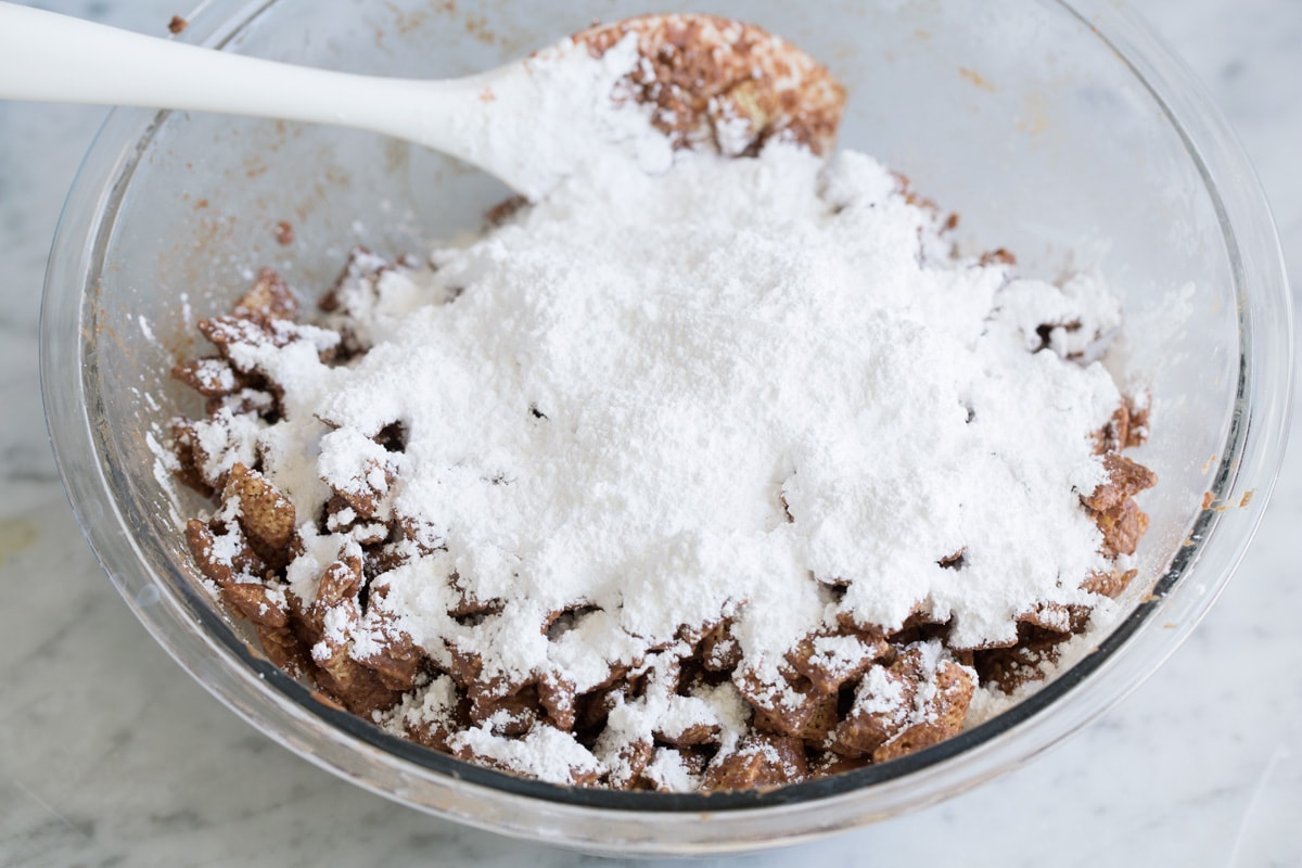 Adding powdered sugar to puppy chow mixture.