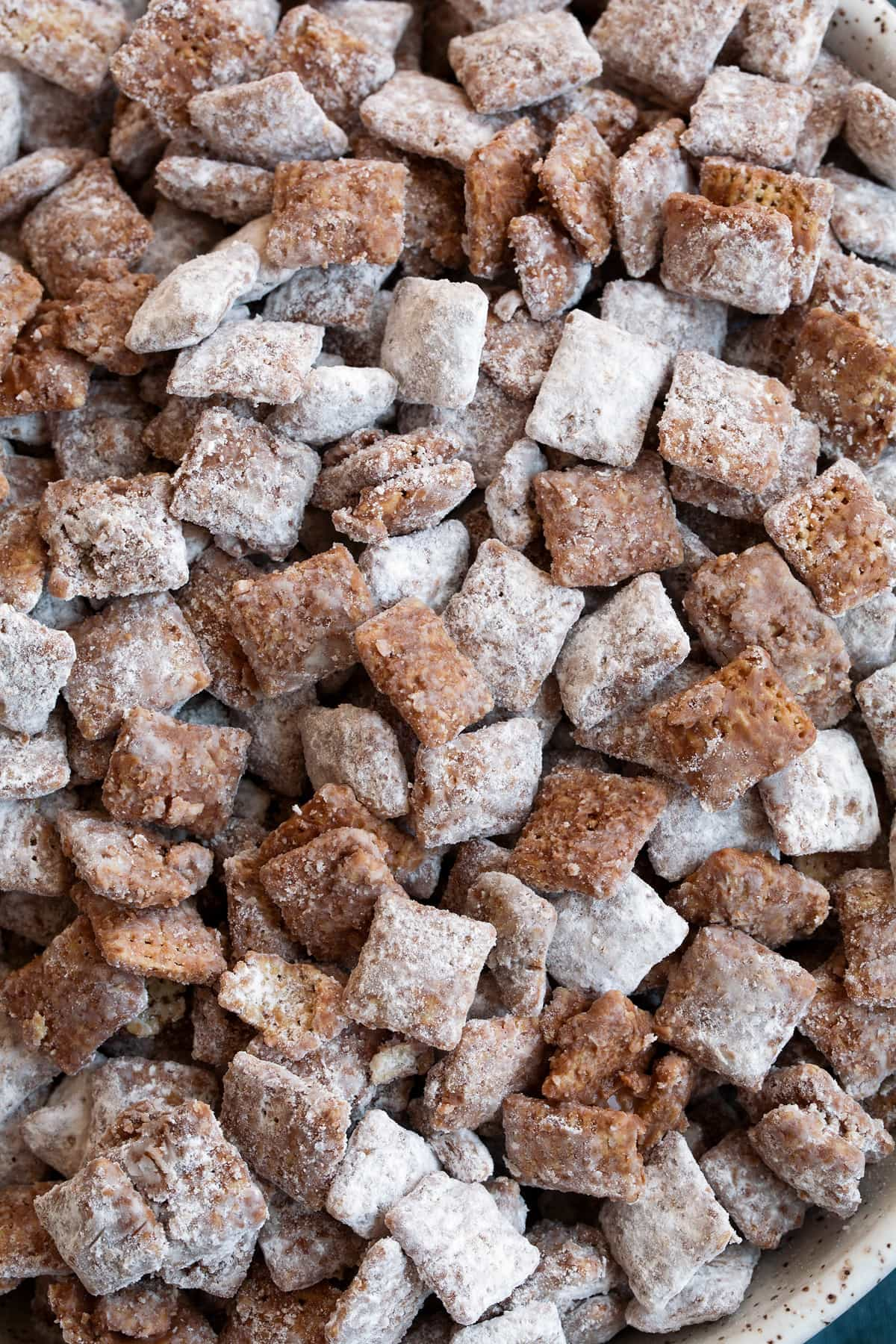 Close up image of muddy buddies showing texture of chocolate coating, powdered sugar and cereal.