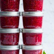 Raspberry jam in small glass mason jars.