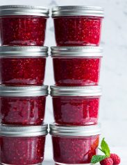Raspberry jam in small glass mason jars.