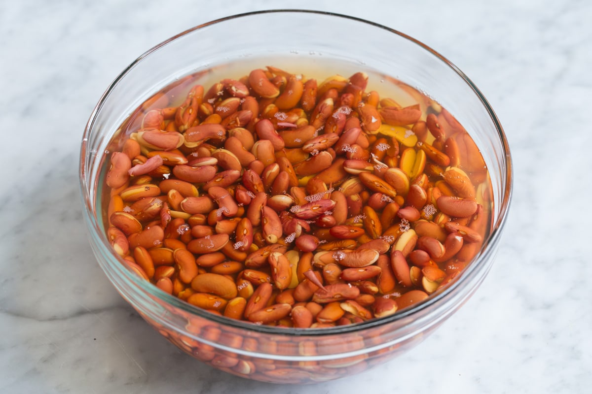 Red beans soaking in a glass bowl with water.