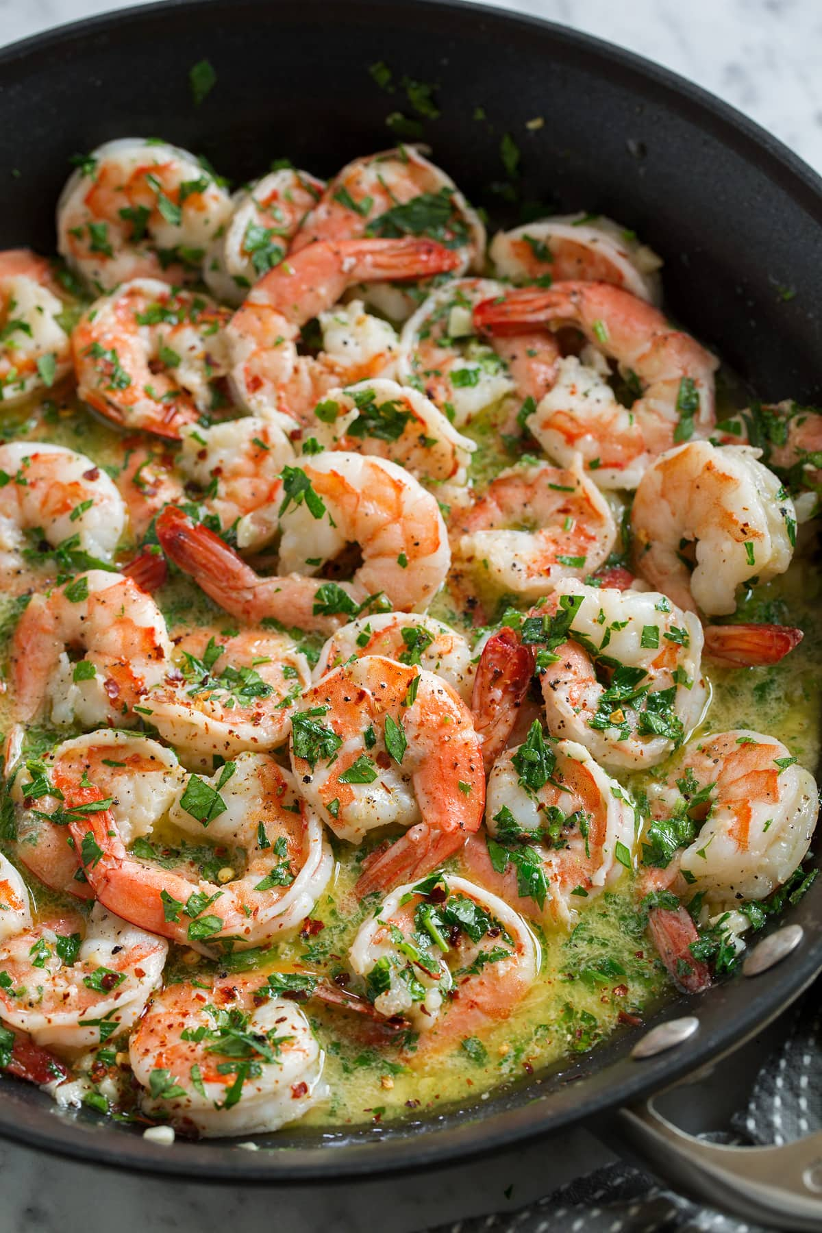 Shrimp scampi in a black skillet with sauce.