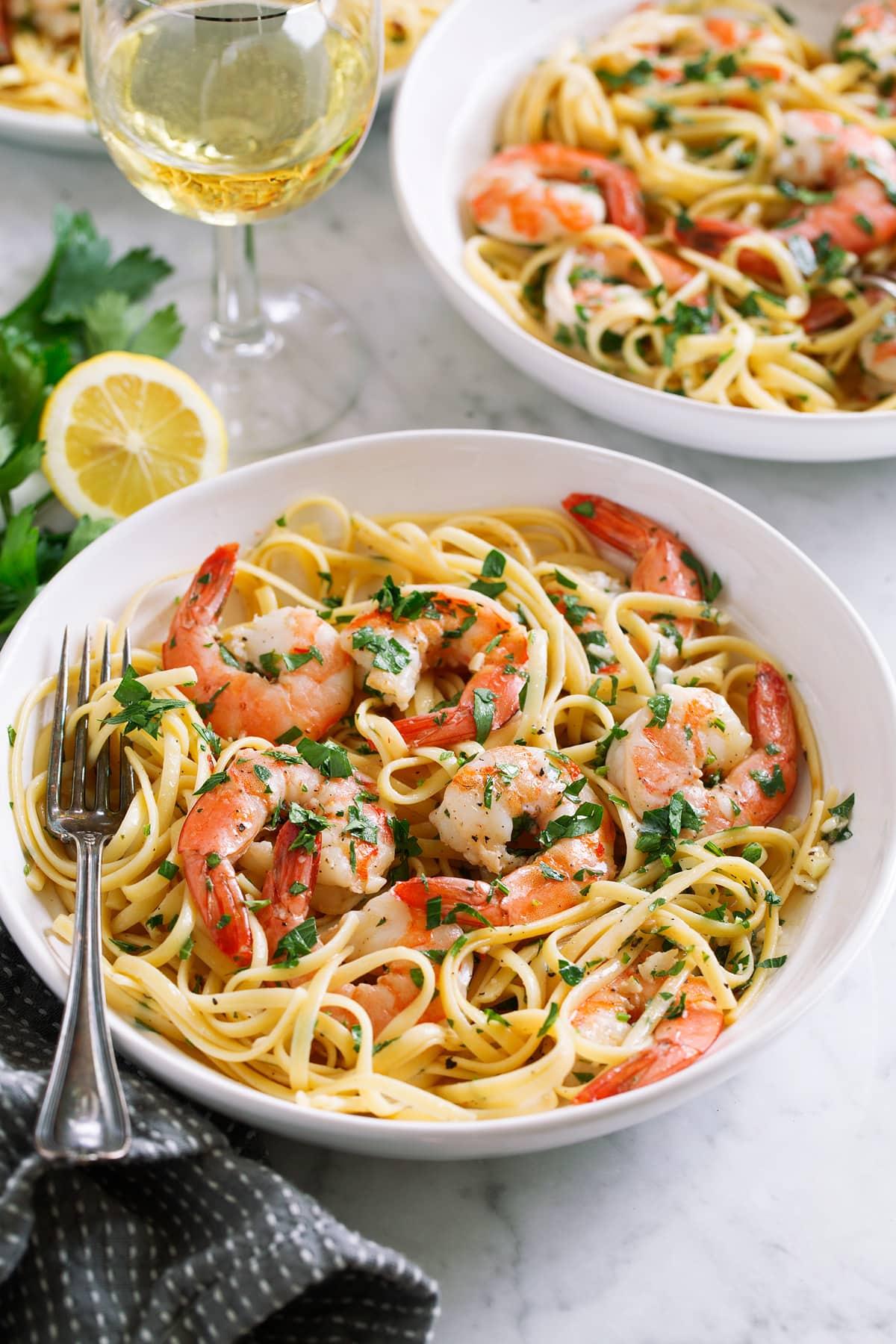 Shrimp scampi servings in pasta bowls.