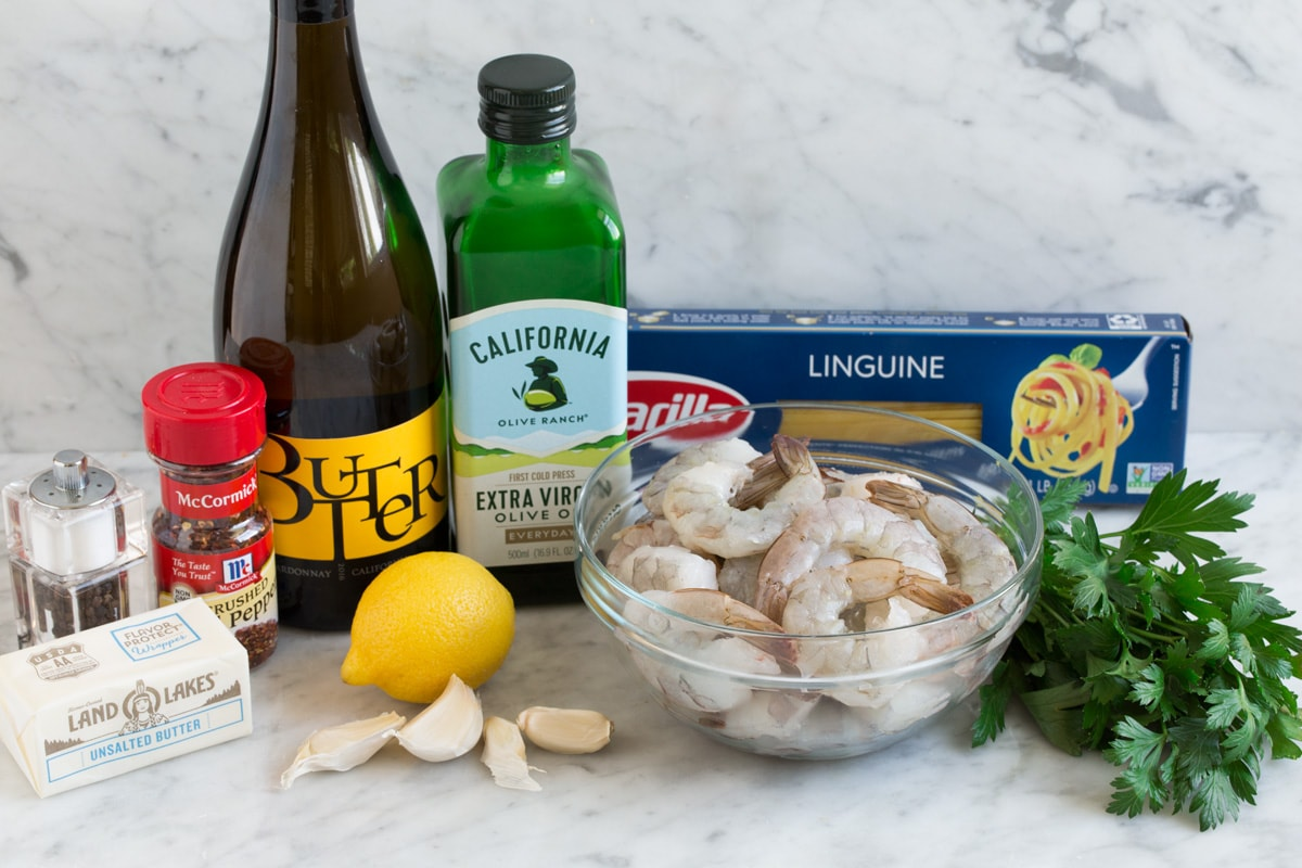 Shrimp scampi ingredients shown here including shrimp, wine, lemon, garlic, butter, olive oil, shrimp, parsley, red pepper flakes, salt and pepper, and pasta.