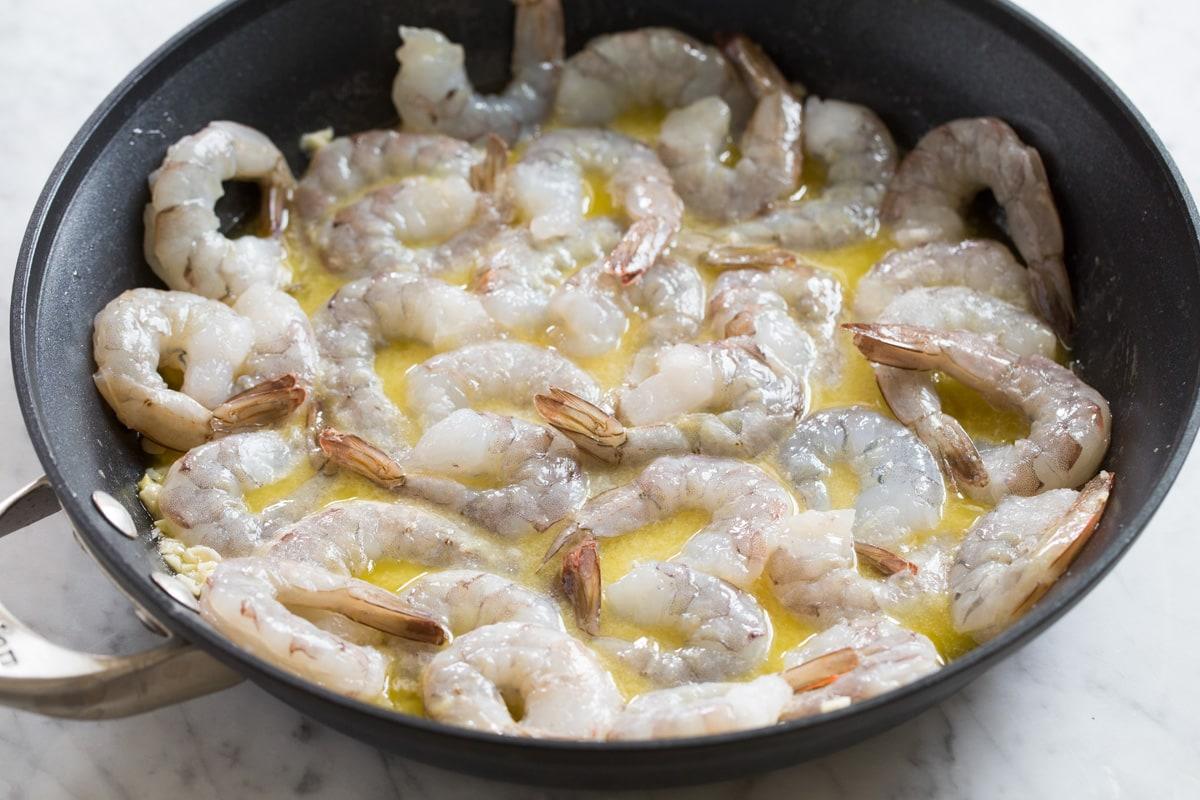 Sauteing shrimp in scampi sauce.