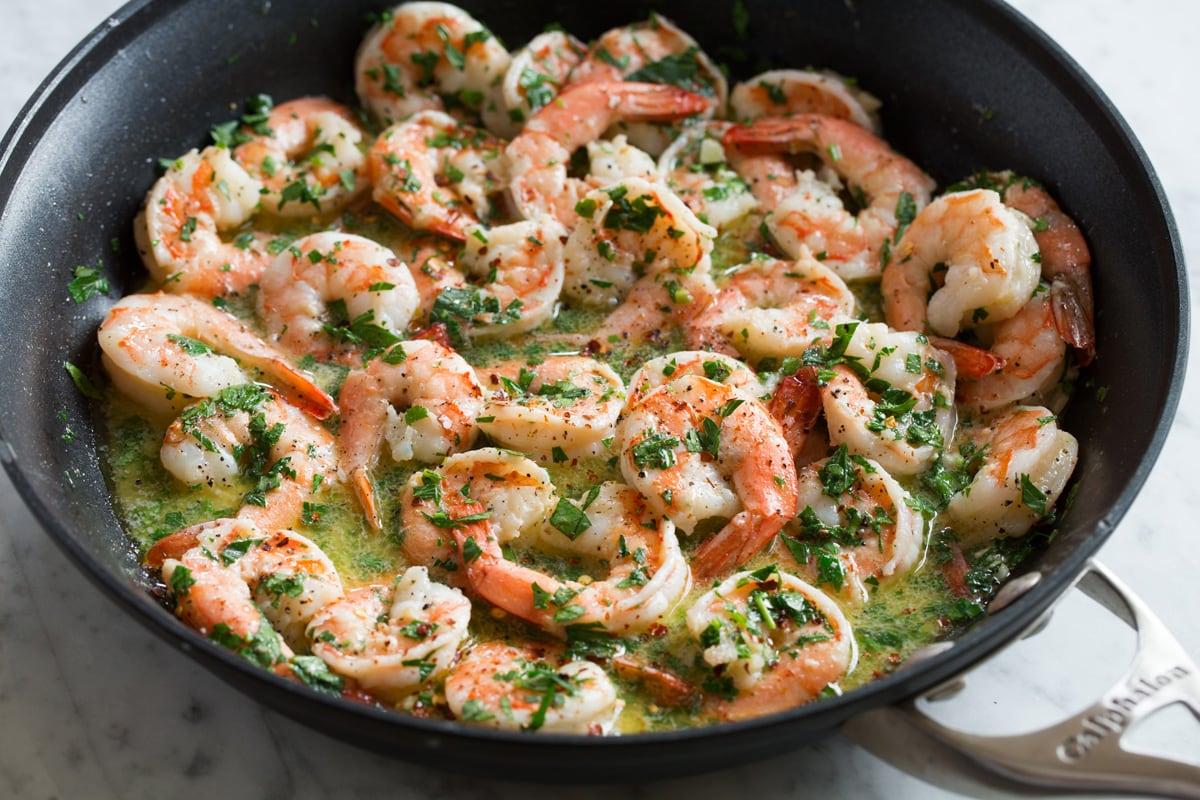 Herbs added to shrimp scampi in skillet.