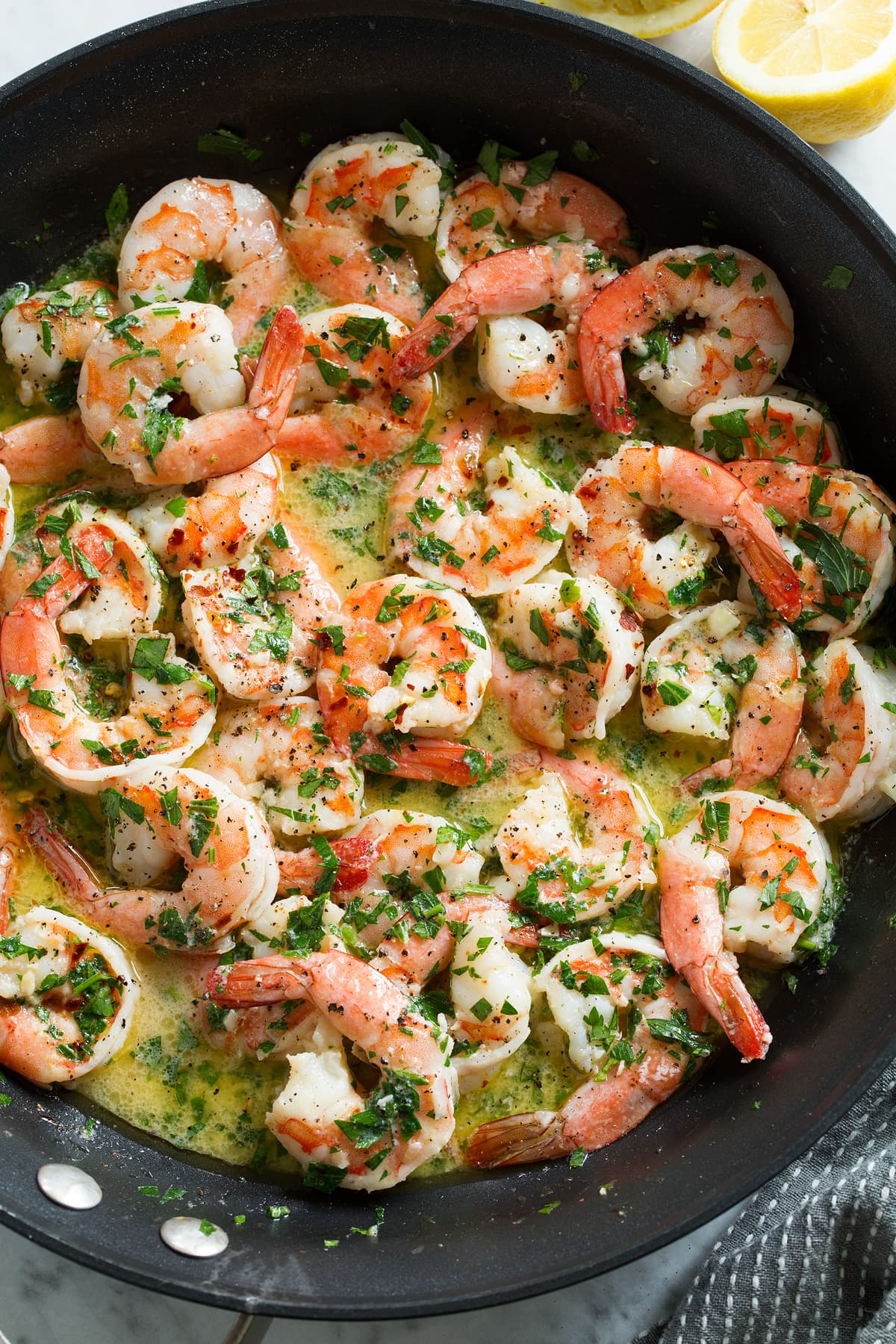 Overhead close up image of shrimp scampi in a skillet after cooking.