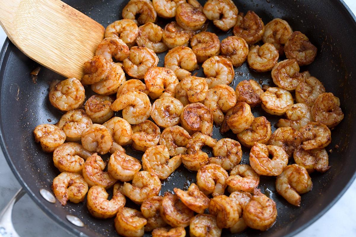 Cooking seasoned shrimp in a skillet.