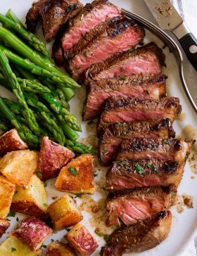Marinated grilled steak on a serving plate with a side of asparagus and potatoes.