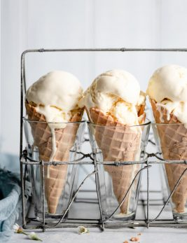 Three ice cream cones in a vintage wire and glass stand.
