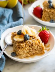 Slice of baked oatmeal topped with fresh fruit and maple syrup.
