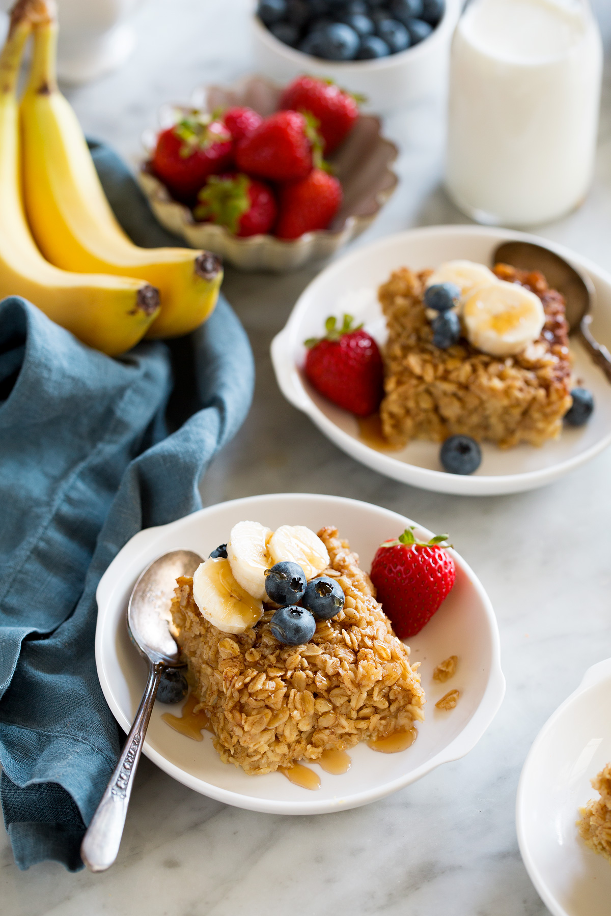 Squares of baked oatmeal topped with fresh fruit in white serving bowls.