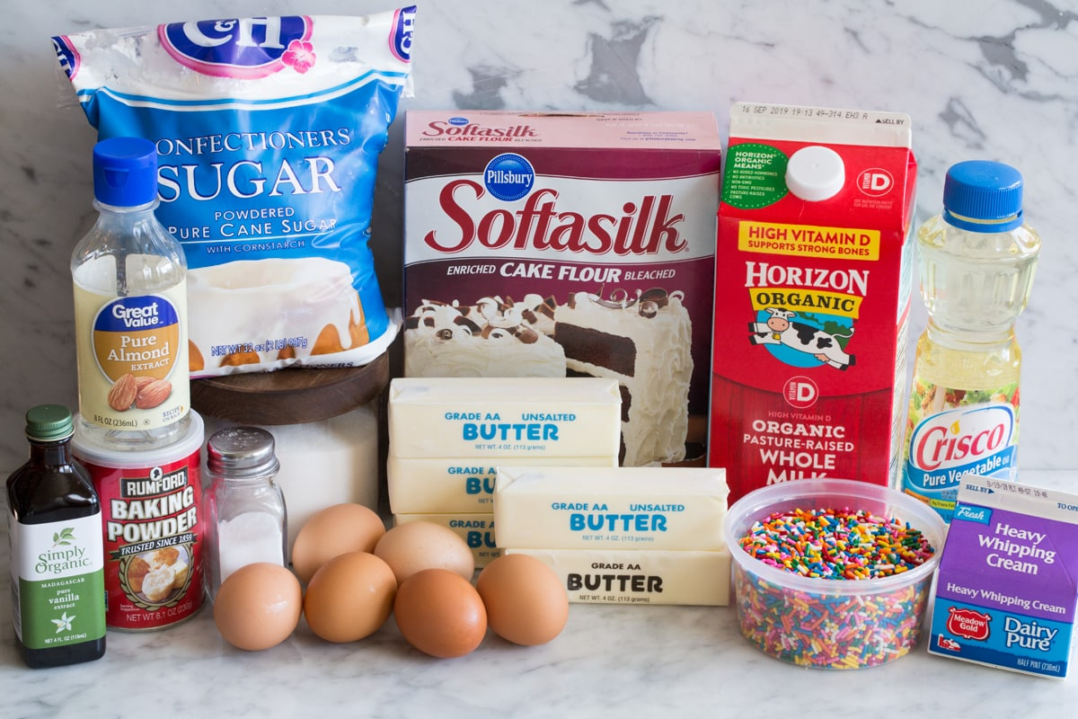 Funfetti Birthday Cake ingredients including cake flour, butter, sugar, eggs, egg whites, vanilla, almond extract, milk, sprinkles, vegetable oil, cream, salt, baking powder and powdered sugar.