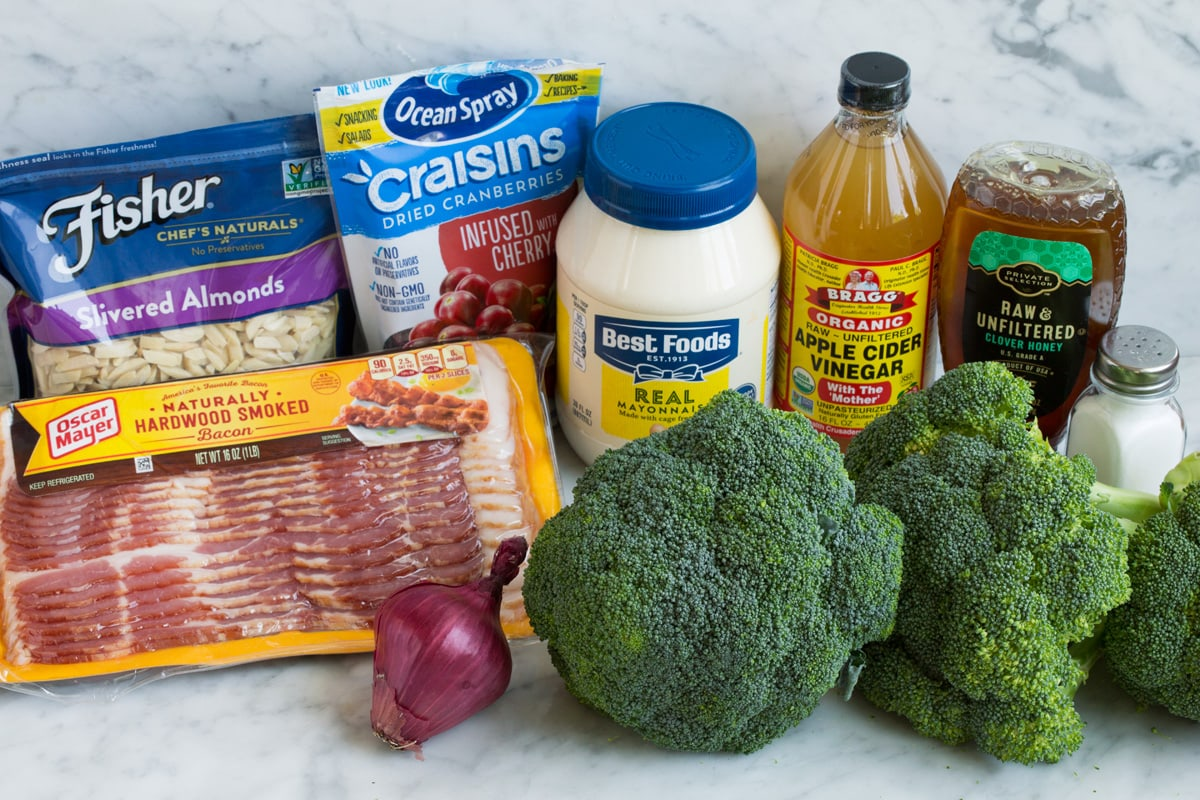 Ingredients to make broccoli salad shown here including broccoli, salt, honey, apple cider vinegar, mayonnaise, dried cranberries, slivered almonds, bacon and red onion.