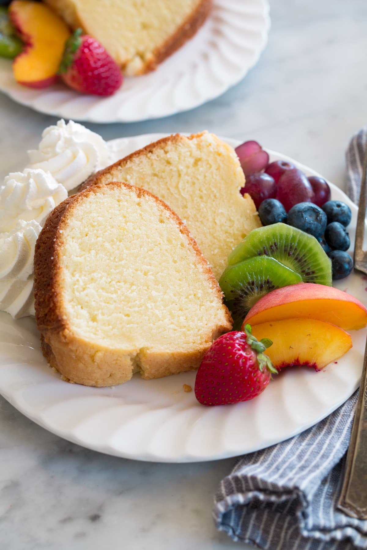 Slice of pound cake on a dessert plate with a side of fresh fruit and whipped cream.