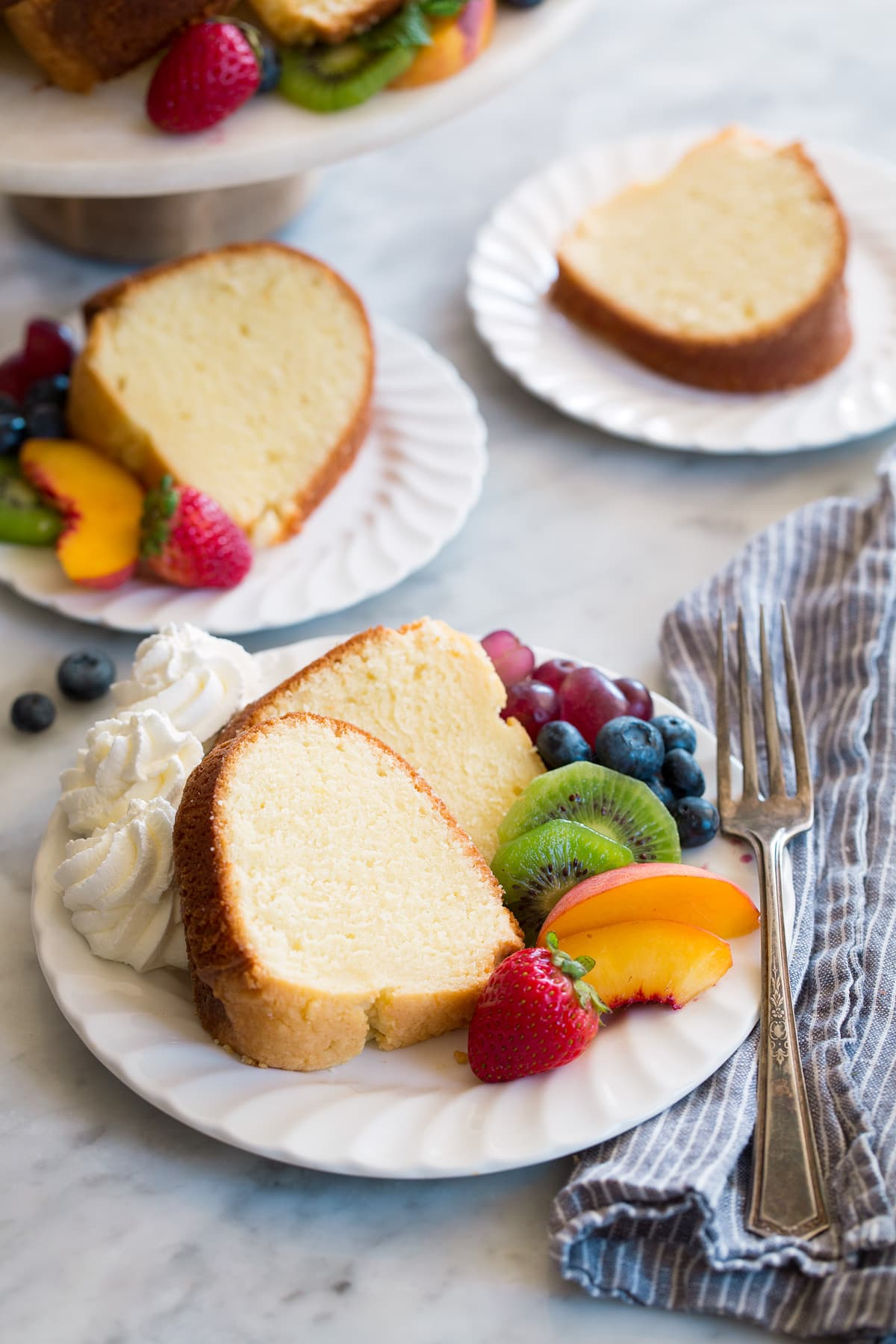 Three white dessert plates with slices of homemade pound cake.