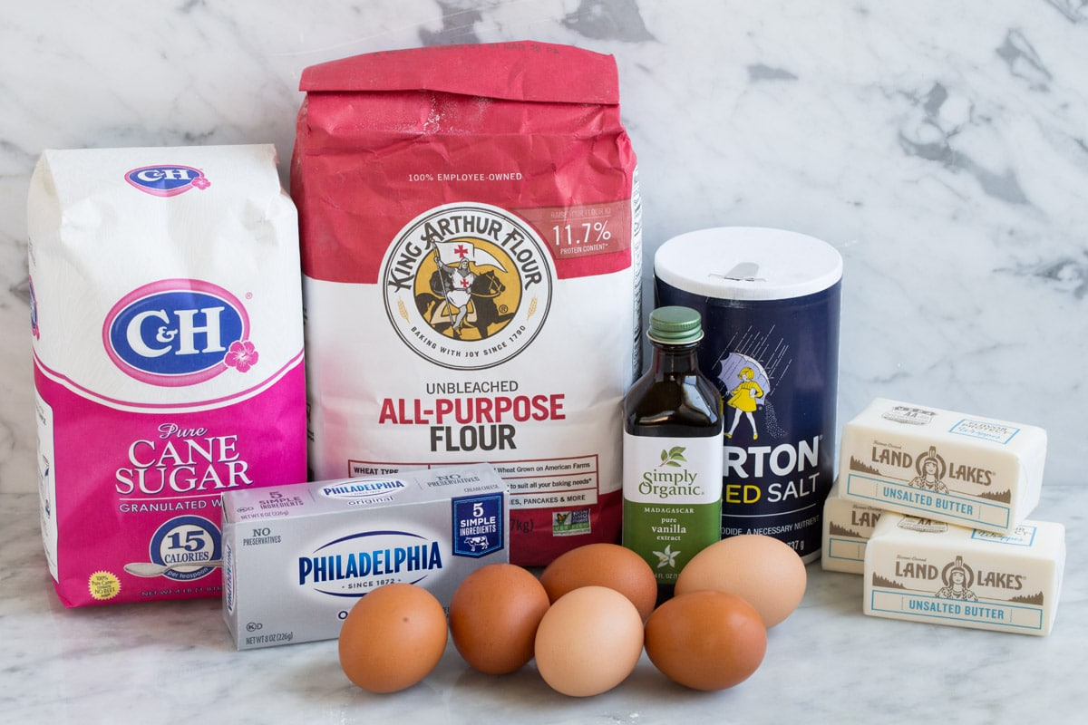 Ingredients to make pound cake shown here including flour, sugar, butter, cream cheese, eggs, salt and vanilla.