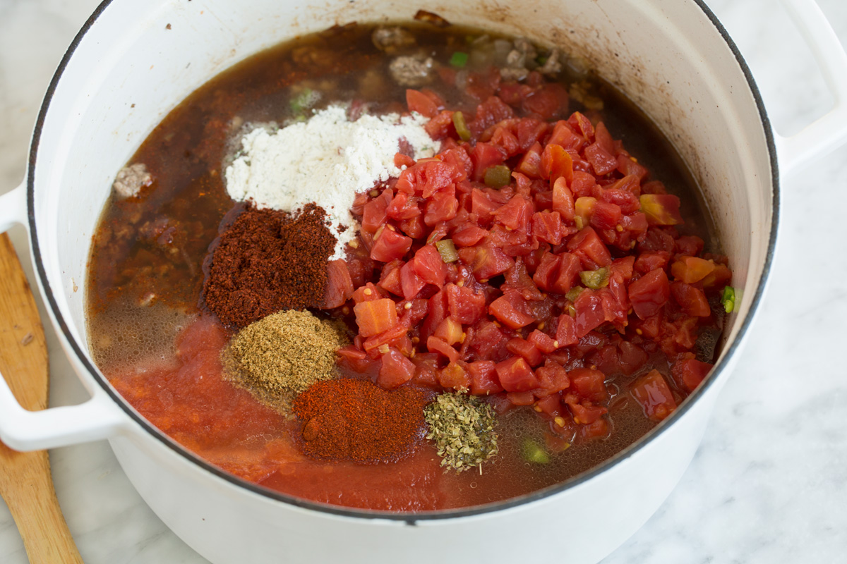 Adding tomatoes and spices to pot to make taco soup.
