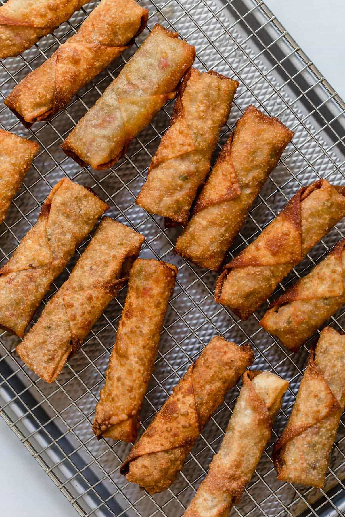 Egg rolls on a cooling rack set over a baking sheet.
