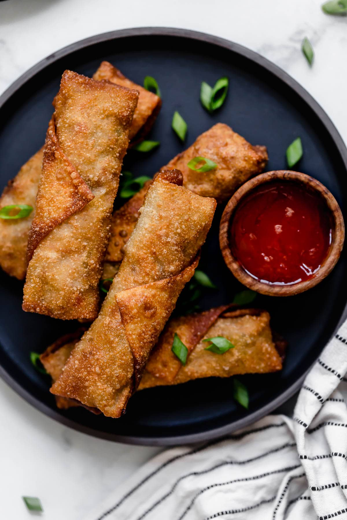 Five egg rolls on a dark plate with a side of dipping sauce.