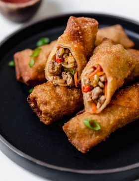 Egg rolls stacked on a black plate with one cut in half to show exterior.