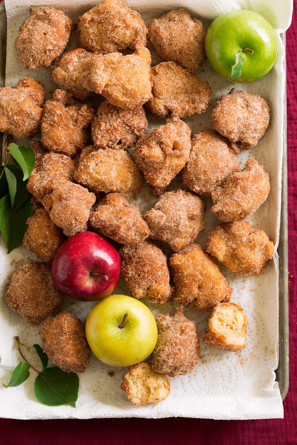 Apple fritters on a baking sheet covered with a paper towel.