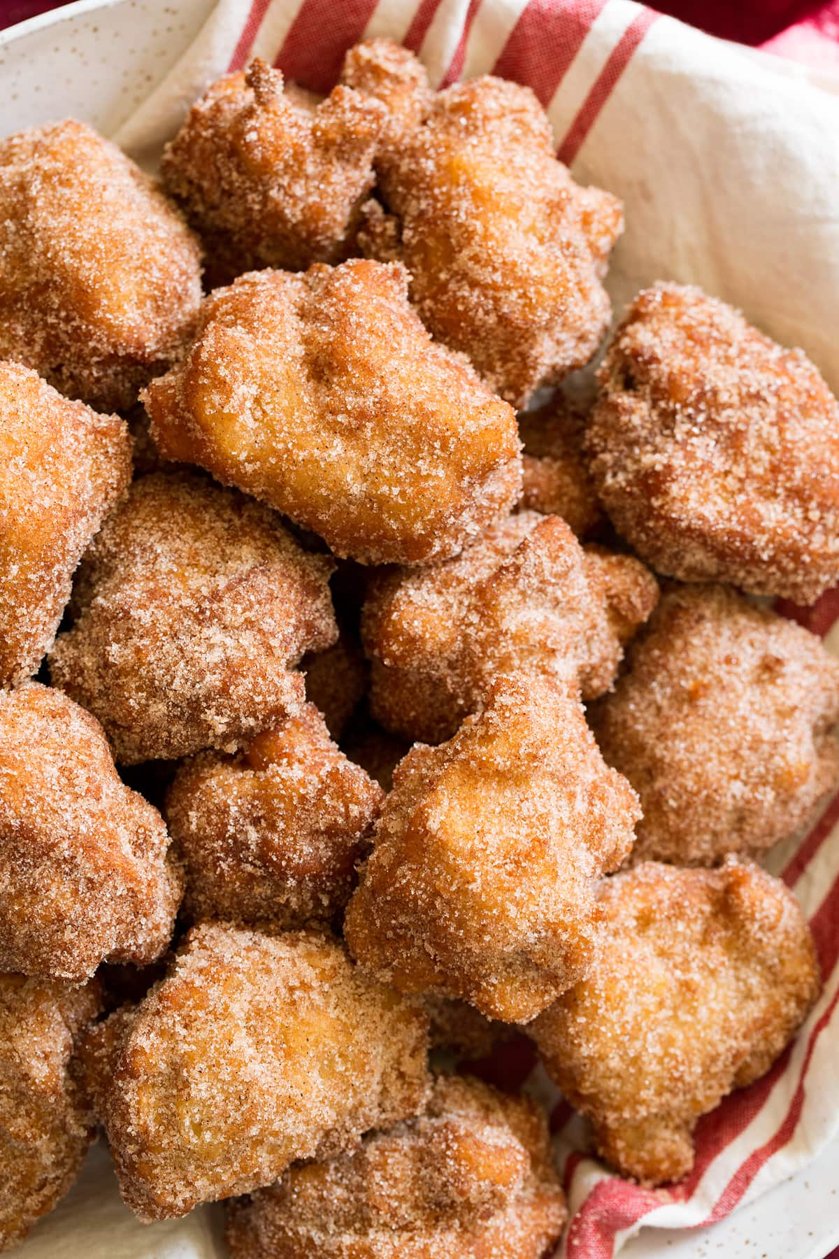 Close up image of apple fritters coated in cinnamon sugar.